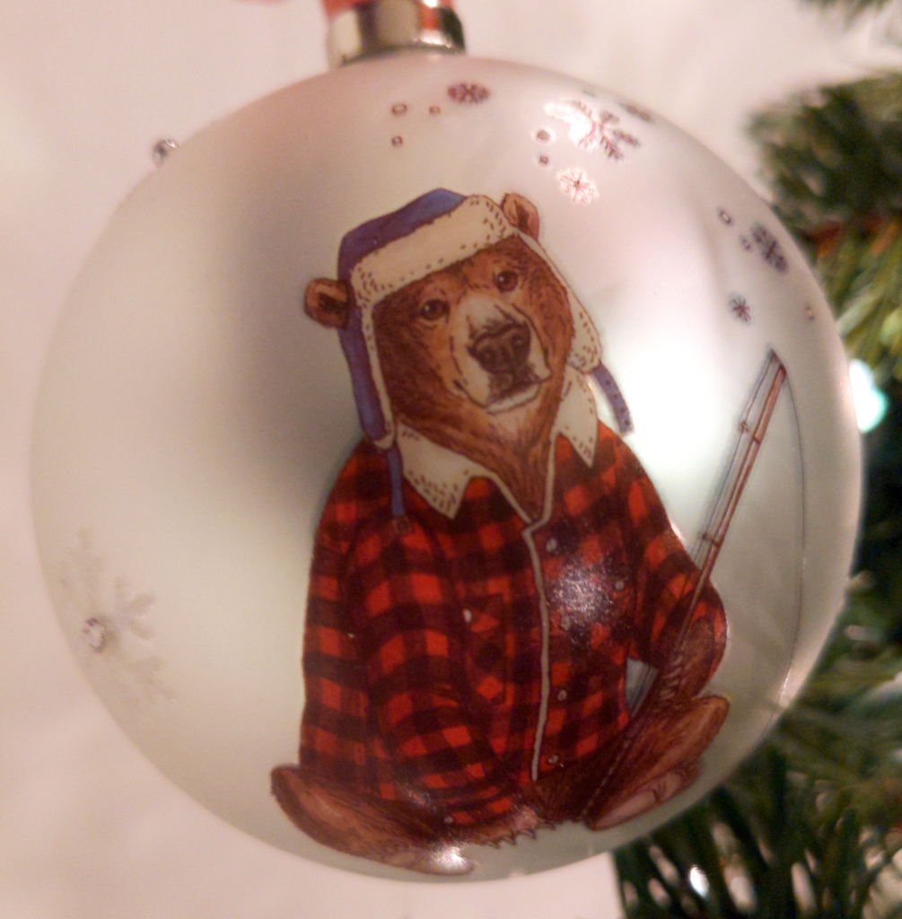 A brown bear wearing a plaid coat and a blue floppy hat lined with fleece and holding a fishing rod. This image is on a silver ball that has sparkly snowflakes sporadically in the background.