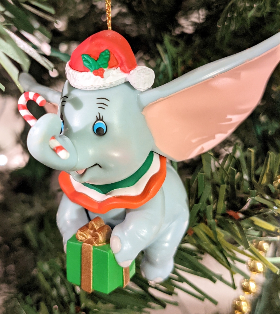 Christmas tree ornament - Dumbo, an elephant with very large ears, is wearing a red Santa hat with holly berry on it, is holding a red and white candy cane with his trunk, and is holding a green present with gold ribbon with his front feet. He looks very happy.