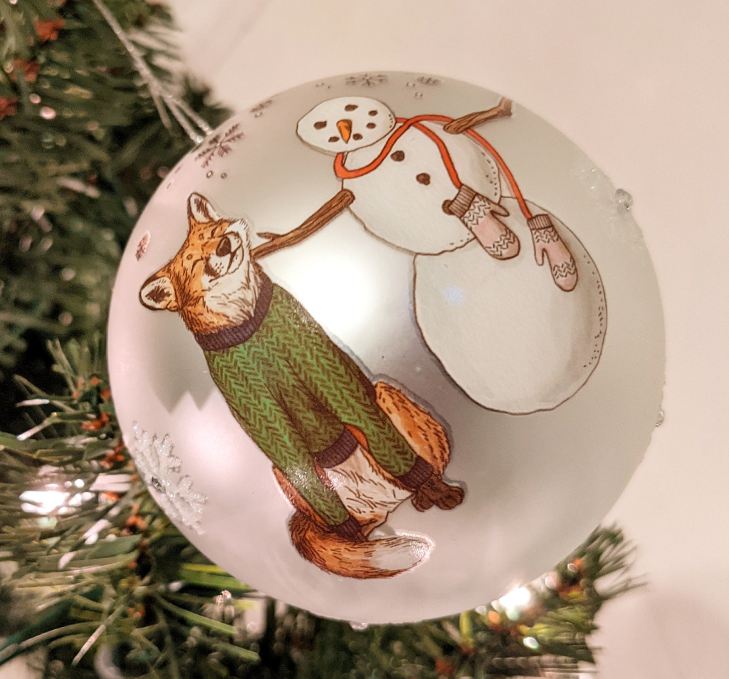 A red fox wearing a green sweater happily rubs its chin against a snowman. This image is on a silver ball that has sparkly snowflakes sporadically in the background.