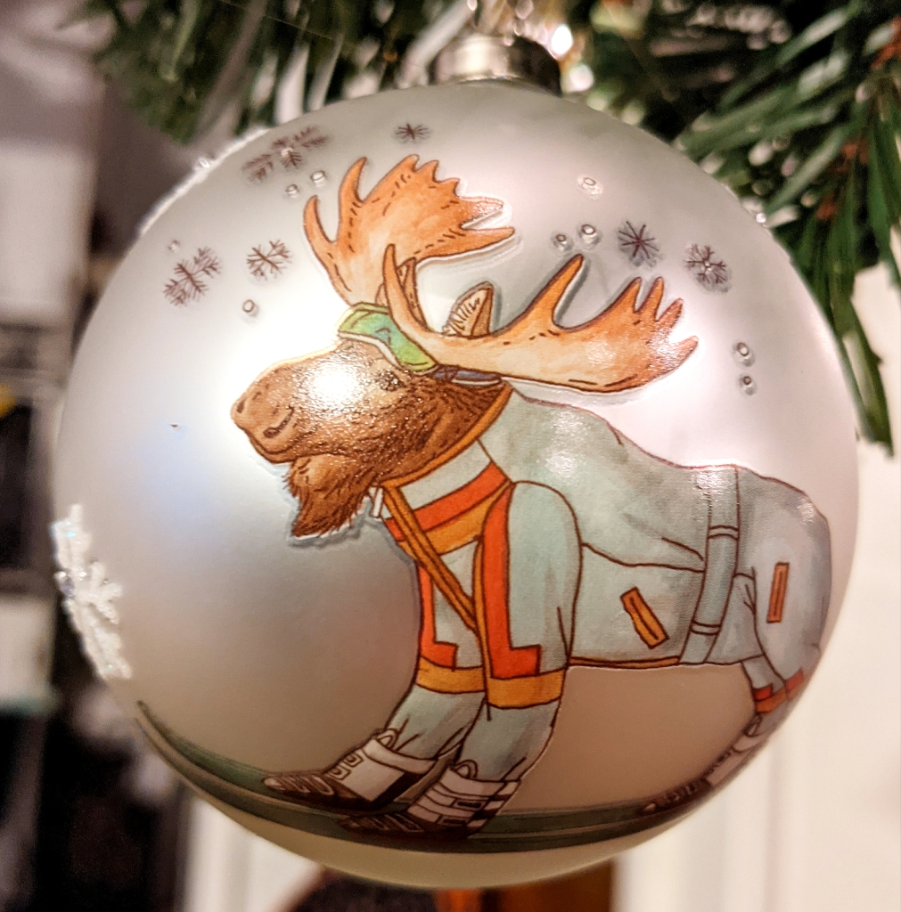 A brown moose wearing green snow goggles and a white ski suit with orange accents rides on a pair of skis. This image is on a silver ball that has sparkly snowflakes sporadically in the background.