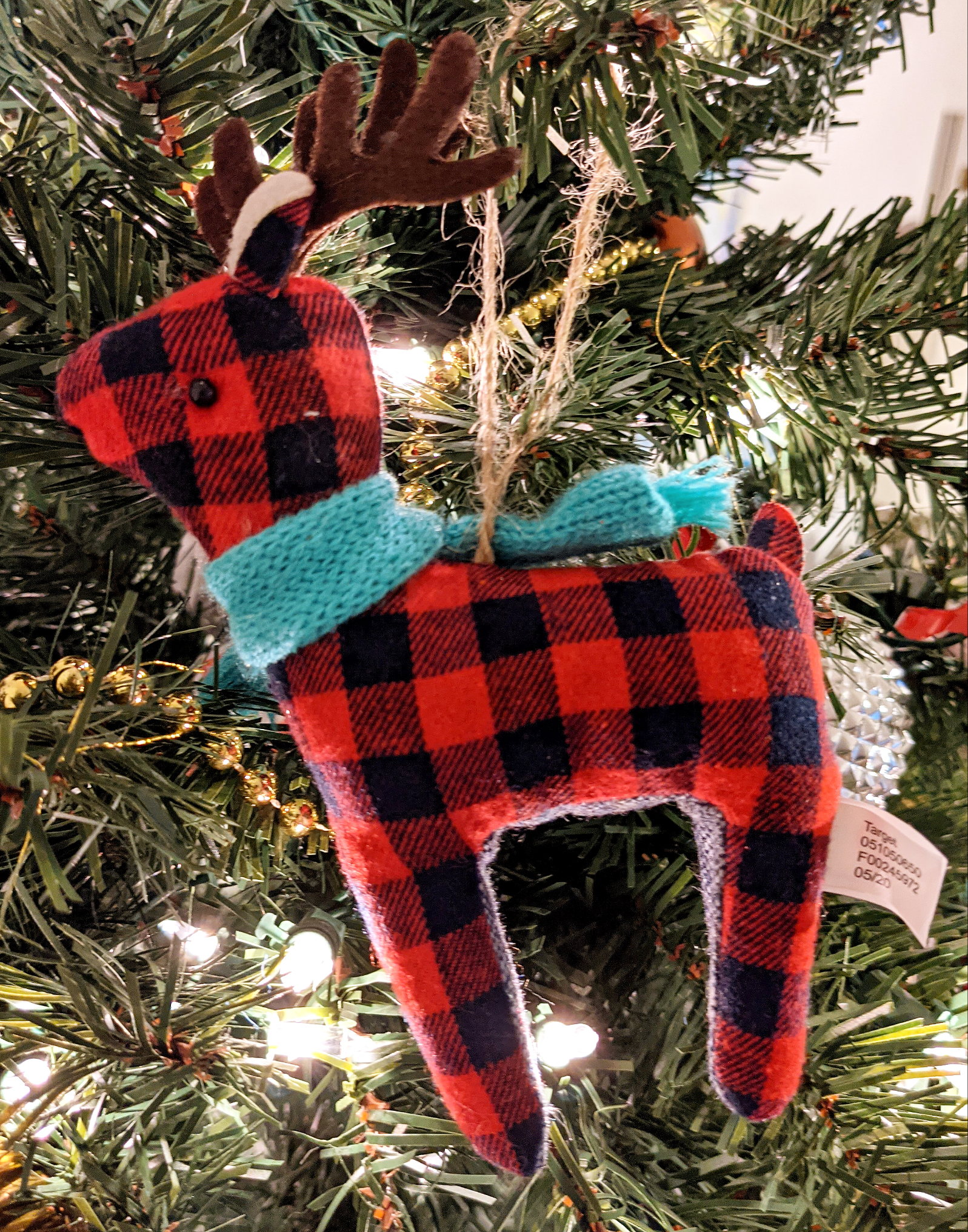 A black and red plush reindeer with brown antlers and black beads for eyes wears a green scarf.