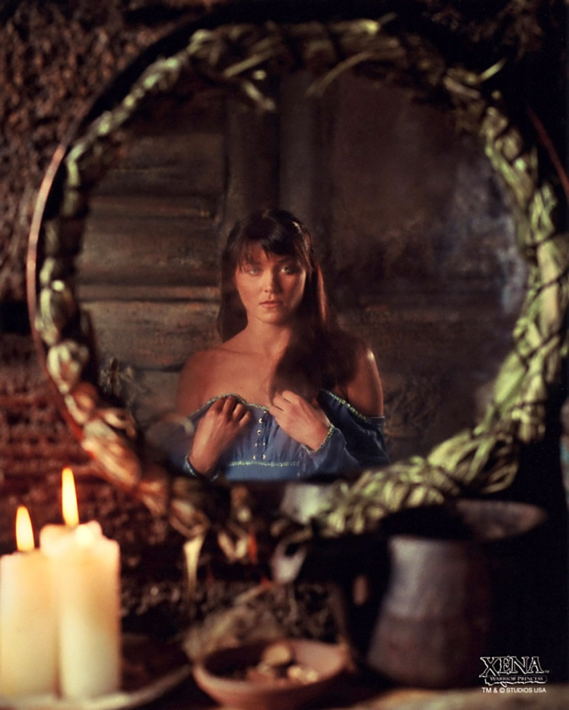 Xena, a dark-haired white woman, looks into a circular mirror as she puts on a blue dress. She looks uncomfortable and pensive, like wearing a dress is unnatural.